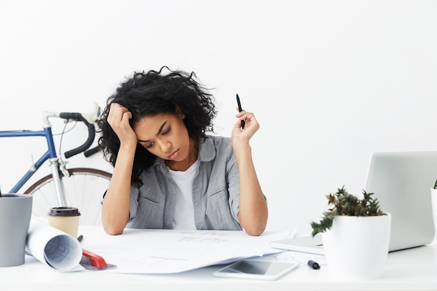 Jovem engenheira infeliz trabalhando em casa em um grande projeto Foto gratuita