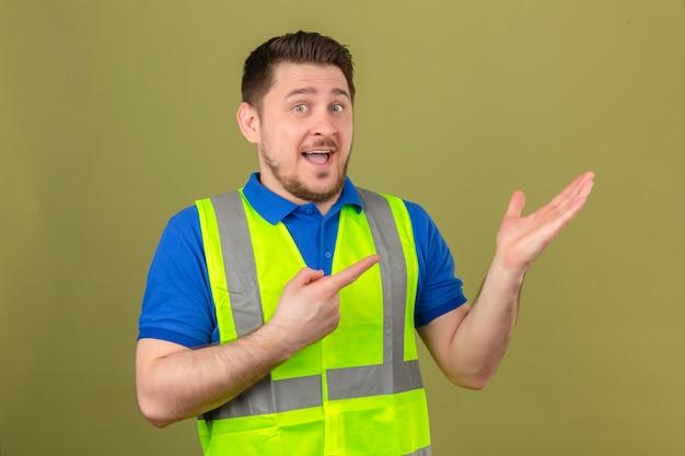Jovem engenheiro vestindo colete de construção, sorrindo para a câmera enquanto se apresenta com a mão e aponta com o dedo sobre um fundo verde isolado Foto gratuita