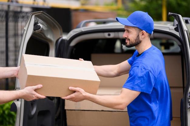Jovem entregador dando parcela ao cliente Foto Premium