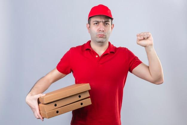 Jovem entregador de camisa polo vermelha e boné segurando caixas de pizza, franzindo a testa levantando o punho com expressão negativa no rosto sobre parede branca isolada Foto gratuita