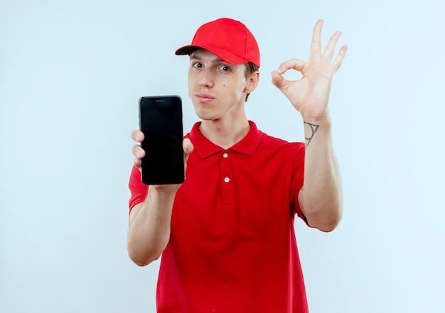Jovem entregador de uniforme vermelho e boné mostrando smartphone mostrando placa de ok em pé sobre uma parede branca Foto gratuita