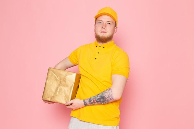 Jovem entregador em polo amarelo boné amarelo jeans branco segurando uma caixa rosa Foto gratuita