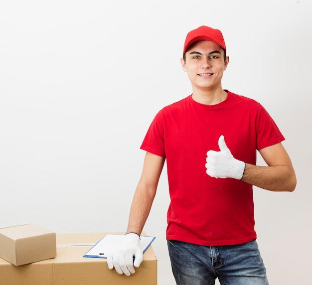 Jovem entregador mostrando sinal ok Foto gratuita