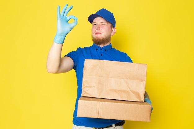 Jovem entregador no polo azul boné azul jeans branco mochila segurando caixas em amarelo Foto gratuita