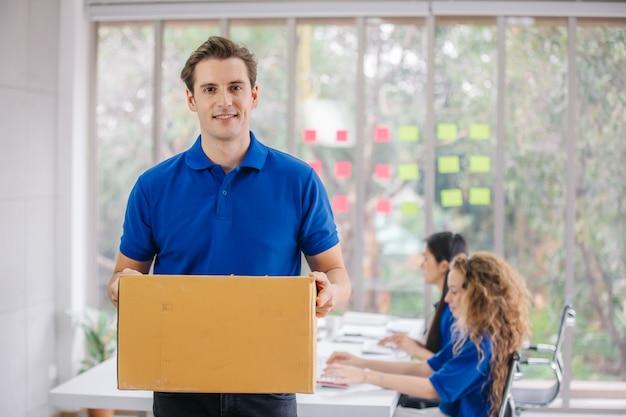 Jovem entregador segurando uma caixa de papelão no escritório de entrega. Foto Premium
