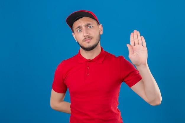 Jovem entregador vestindo camisa pólo vermelha e boné em pé com a mão aberta, fazendo sinal de pare com gesto de defesa de expressão sério e confiante sobre fundo azul isolado Foto gratuita