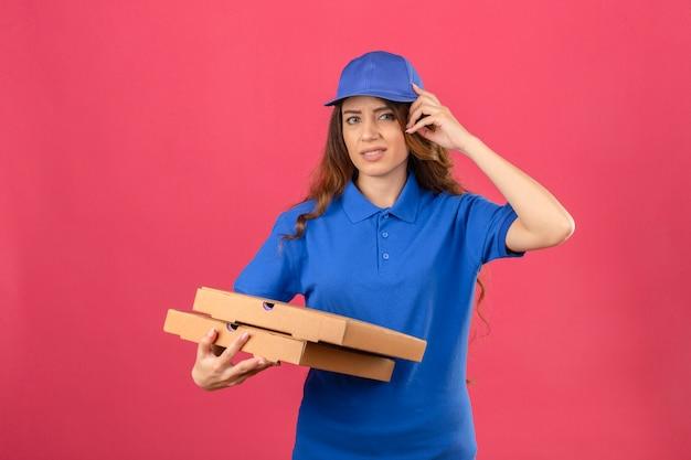 Jovem entregadora com cabelo encaracolado, vestindo uma camisa pólo azul e boné com a mão na cabeça por engano, lembre-se do erro esqueceu o conceito de memória ruim sobre fundo rosa isolado Foto gratuita