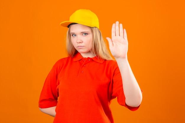 Jovem entregadora de camisa pólo vermelha e boné amarelo em pé com a mão aberta, fazendo sinal de pare com gesto de defesa de expressão sério e confiante sobre fundo laranja isolado Foto gratuita