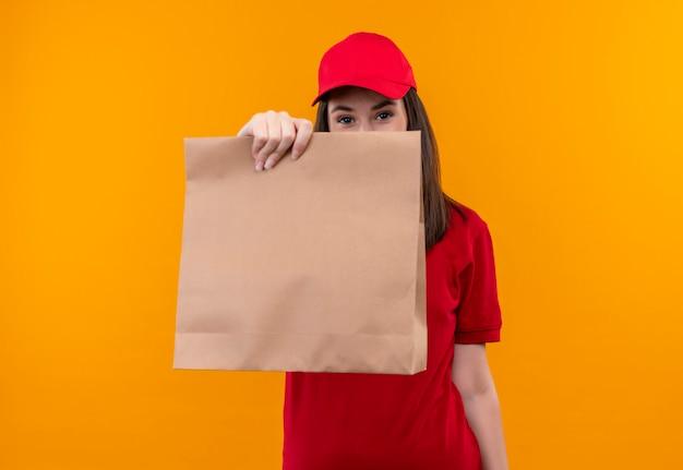 Jovem entregadora de camiseta vermelha com boné vermelho segurando um pacote sobre fundo amarelo Foto gratuita