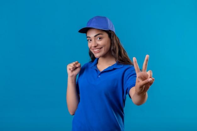 Jovem entregadora de uniforme azul e boné em pé com o punho cerrado, mostrando o sinal da vitória ou número dois, sorrindo alegremente feliz e positiva em pé sobre o fundo azul Foto gratuita