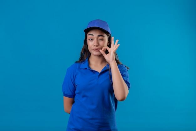 Jovem entregadora de uniforme azul e boné olhando para a câmera piscando e fazendo gesto de silêncio, fazendo o tipo de fechar a boca com um zíper em pé sobre fundo azul Foto gratuita