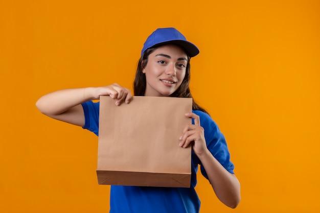 Jovem entregadora de uniforme azul e boné segurando um pacote de papel, olhando para a câmera, sorrindo amigável em pé sobre um fundo amarelo Foto gratuita