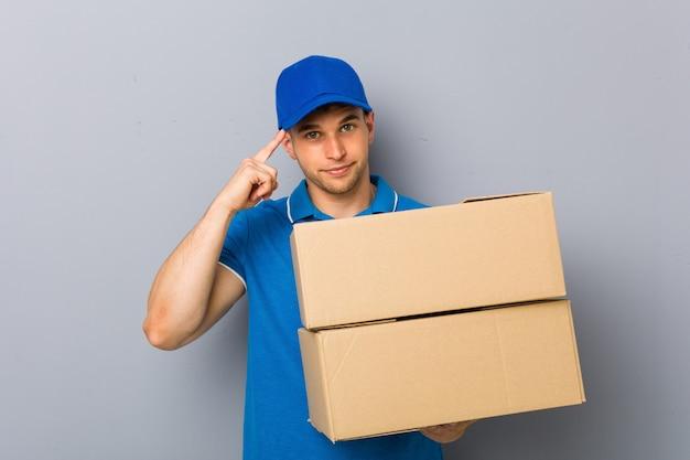 Jovem entregando pacotes apontando seu templo com o dedo, pensando, focado em uma tarefa. Foto Premium