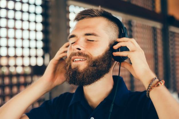 Jovem escuta música em fones de ouvido, usando smartphone, retrato de hipster ao ar livre Foto gratuita