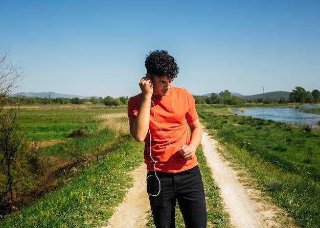 Jovem, escutar, música, ao andar, natural, rastro Foto gratuita