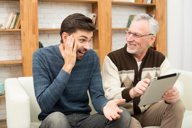 Jovem espantado e envelhecido homem alegre usando tablet no canapé Foto gratuita