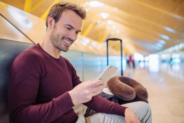 Jovem esperando usando telefone celular no aeroporto com uma mala Foto Premium