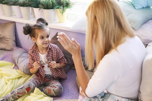 Jovem está brincando com a mãe perto da janela Foto gratuita