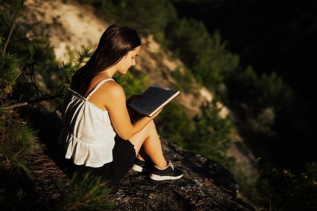 Jovem está lendo um livro, enquanto está sentado contra um belo cenário da natureza. Foto Premium
