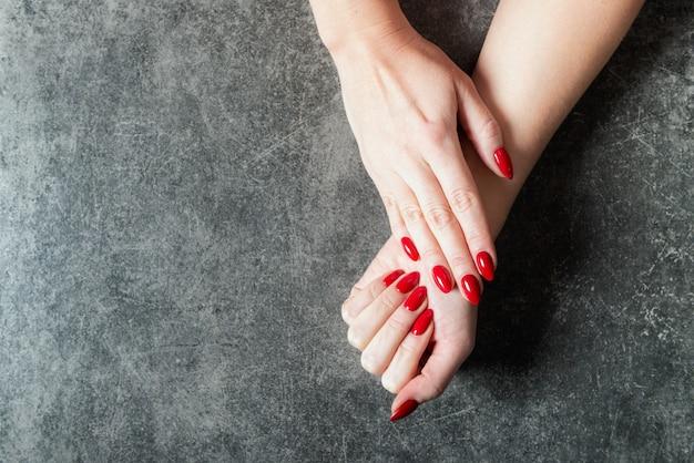 Jovem está mostrando suas unhas vermelhas manicure Foto Premium