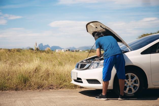 Jovem está verificando carros. Foto Premium