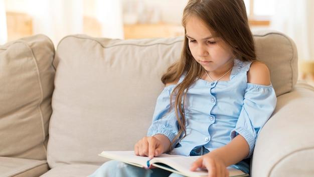 Jovem estudando em casa no sofá com espaço de cópia Foto gratuita