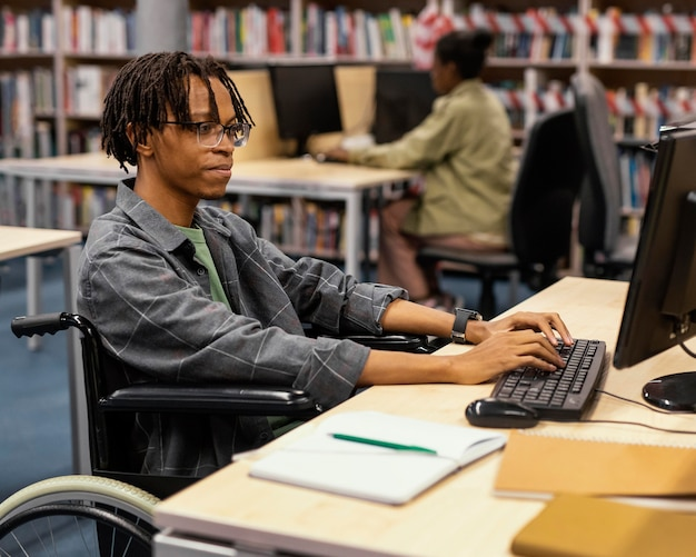 Jovem estudando na biblioteca da universidade Foto gratuita