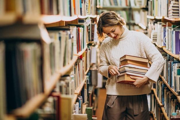 Jovem estudando na biblioteca Foto gratuita