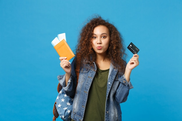 Na imagem uma mulher segurando nas mão direita algumas passagens de avião e um passaporte e na mão esquerda está segurando um cartão de crédito.  | Como organizar uma viagem para qualquer lugar no mundo