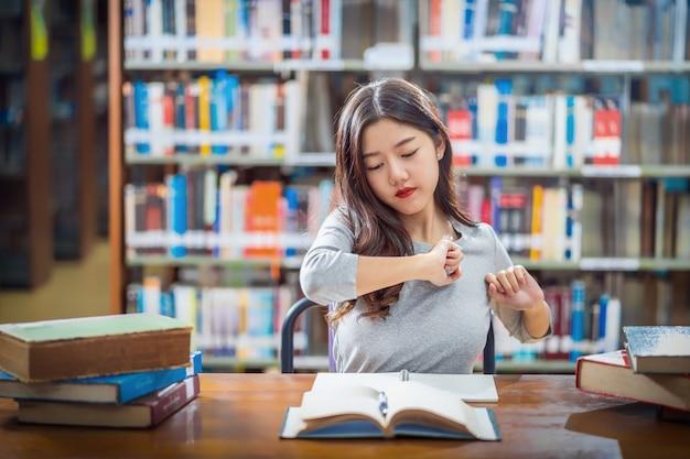 Jovem estudante asiática em terno casual, lendo e fazendo esticar-se na  biblioteca da universidade ou