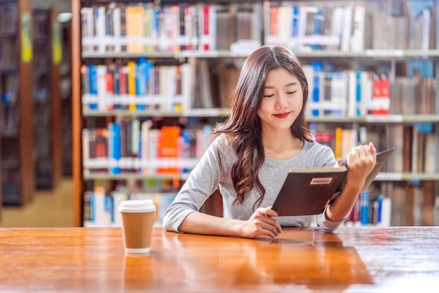 Jovem estudante asiática em terno casual, lendo o livro com uma xícara de café na biblioteca da universidade ou colega na mesa de madeira sobre a parede da estante de livros, volta ao conceito de escola Foto Premium