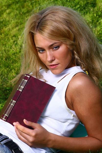 Jovem estudante atraente lendo o livro Foto gratuita