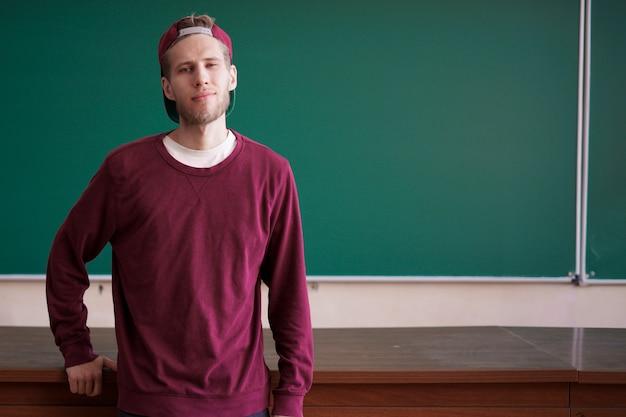 Jovem estudante barbudo senta-se na mesa da mesa do professor na frente do quadro-negro com espaço de cópia Foto Premium