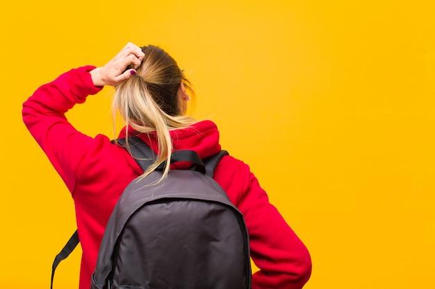Jovem estudante bonita pensando ou duvidando, coçando a cabeça, sentindo-se confuso e confuso, vista traseira ou traseira Foto Premium