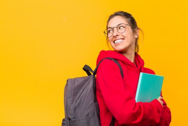 Jovem estudante bonita sorrindo alegremente, sentindo-se feliz, satisfeito e relaxado, com os braços cruzados e olhando para o lado Foto Premium