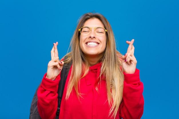 Jovem estudante bonita sorrindo e cruzando ansiosamente os dois dedos, sentindo-se preocupada e desejando ou esperando boa sorte Foto Premium