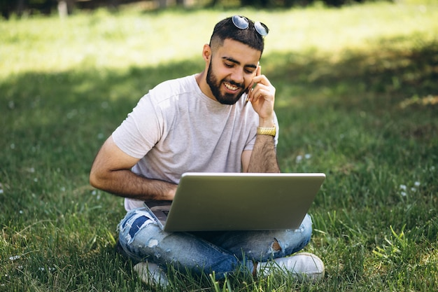 Jovem estudante bonito com laptop em um parque da universidade Foto gratuita