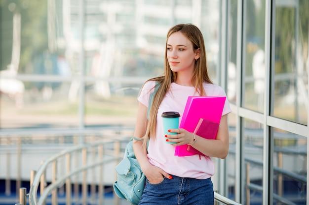Jovem estudante com uma xícara de café na rua Foto Premium