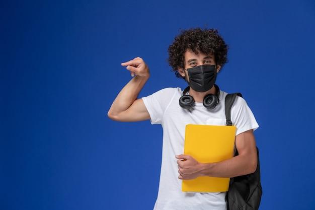 Jovem estudante do sexo masculino de vista frontal em t-shirt branca usando máscara preta e segurando arquivos amarelos sobre o fundo azul claro. Foto gratuita