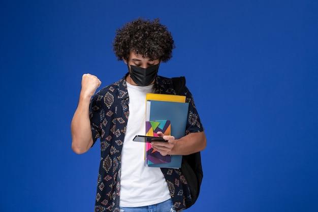 Jovem estudante do sexo masculino de vista frontal usando máscara preta com mochila segurando arquivos e usando seu telefone sobre o fundo azul. Foto gratuita