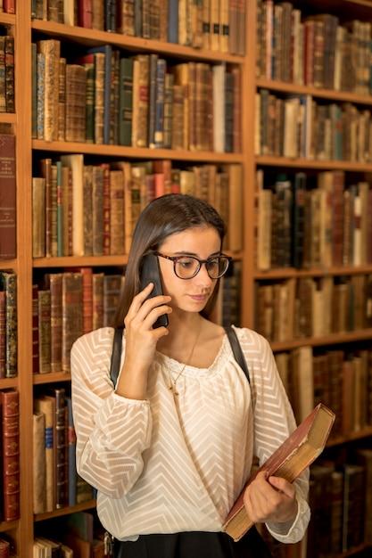 Jovem estudante falando no telefone na biblioteca Foto gratuita