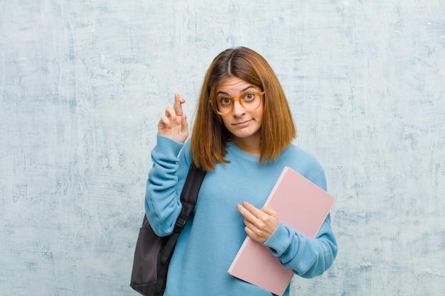 Jovem estudante mulher cruzando os dedos ansiosamente e esperando a boa sorte com um olhar preocupado na parede do grunge Foto Premium