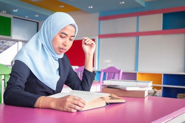 Jovem estudante mulher islâmica. ela está sentada e lendo um livro. Foto Premium