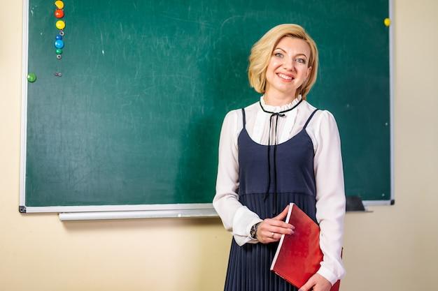 Jovem estudante ou professor sorridente no quadro-negro Foto Premium