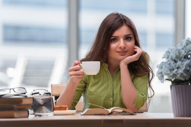 Jovem estudante se preparando para exames bebendo chá Foto Premium