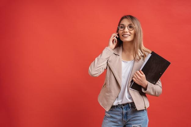 Jovem estudante sorridente ou estagiário em óculos falando ao telefone em pé com uma pasta Foto gratuita