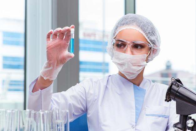 Jovem estudante trabalhando com soluções químicas no laboratório Foto Premium