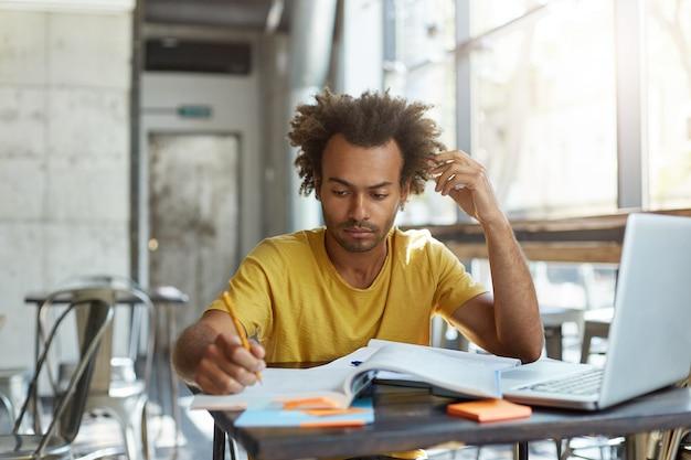 Jovem estudante universitário africano sério e focado em uma camiseta amarela, ocupado fazendo as tarefas de casa, escrevendo no livro de exercícios, sentado no espaço vazio de coworking no início da manhã, usando um laptop Foto gratuita