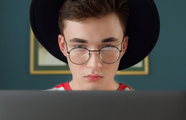 Jovem estudante usando óculos e laptop Foto Premium