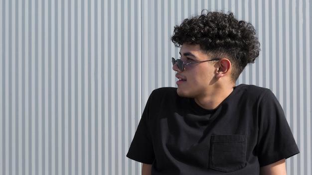 Jovem étnico encaracolado na camisa preta e óculos de sol Foto gratuita